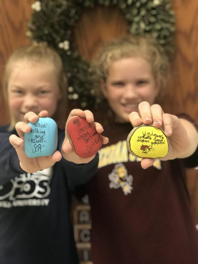 CIS students paint positive messages on rocks to be placed outside the building
