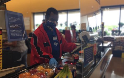 Othello Gooden Jr., essential worker at Kroger, checks out customers using PPE.