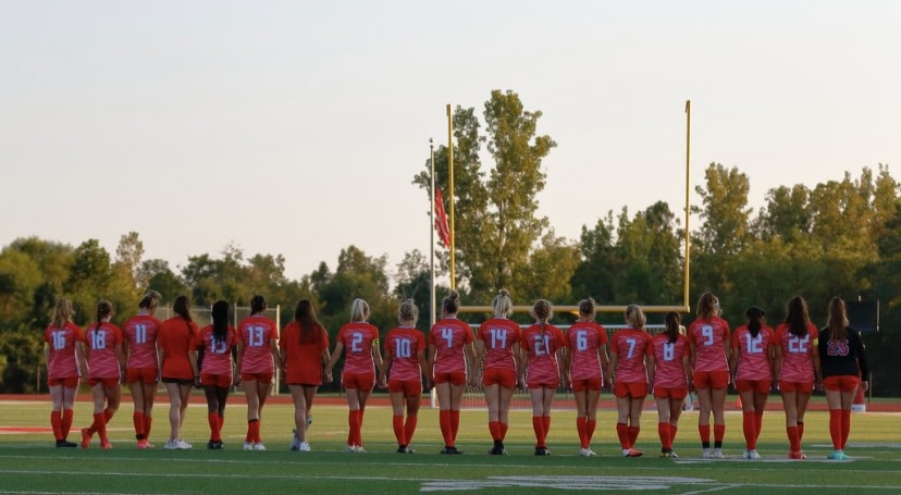 The Lady Knights soccer team singing the national anthem